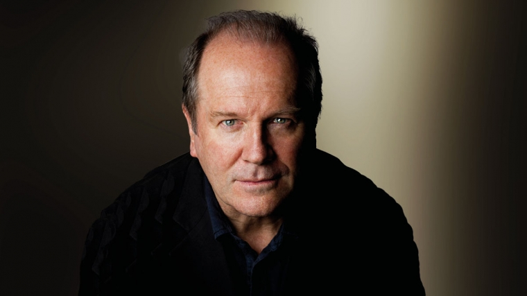 William Boyd looking forward wearing a black shirt, with a moody black and grey background