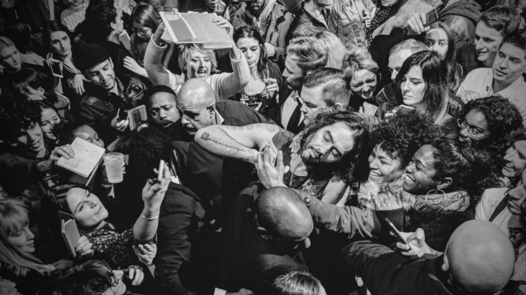 Crowd of fans surrounding Russell Brand