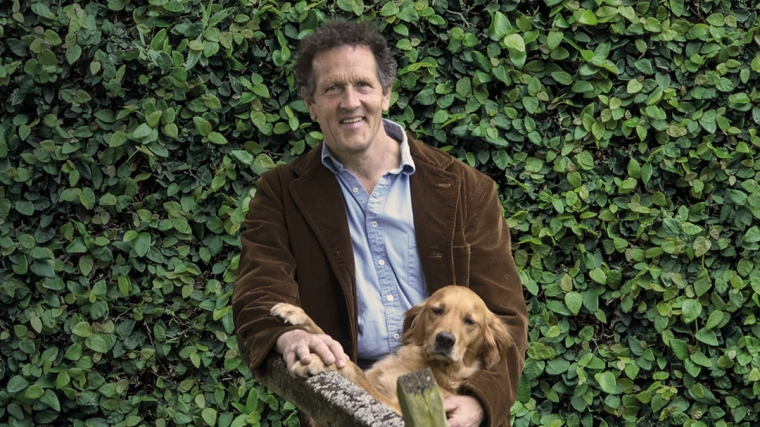 Monty Don standing in front of a green bush, with a dog