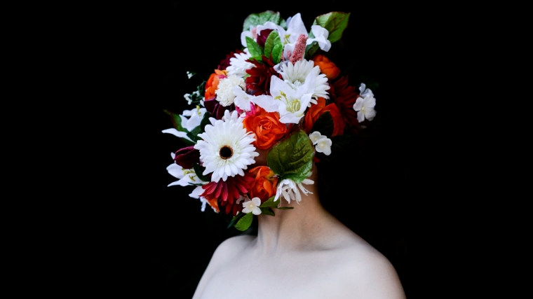 An artistic photographic portrait of flowers over a person's face