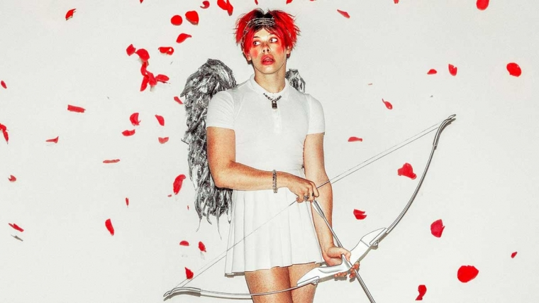 Yungblud with red hair and lipstick wearing a white dress with silver wings and a bow and arrow, surrounded by falling red petals