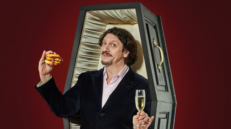 Jay Rayner wearing a suit standing in an open up-right coffin holding a burger in his right hand and a champagne flute in his left, with a deep red background