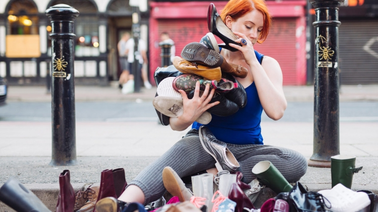 When Did You Stop Dancing? performer sitting on the ground surrounded by piles of shoes