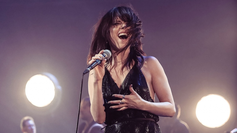 Imelda May singing on stage, with lights behind her