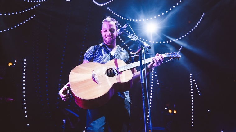 James Morrison with a guitar, on stage at Roundhouse, surrounded by hanging fairy-style lights