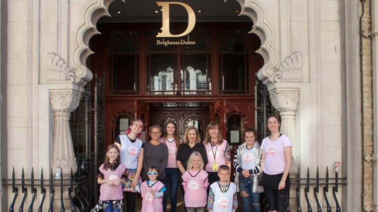 Members of Umbrella Club stand infront of Brighton Dome's gate with staff from Flamingo Chicks and Brighton Dome