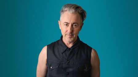 Alan Cumming wearing a dark blue sleeveless shirt with a teal colour background
