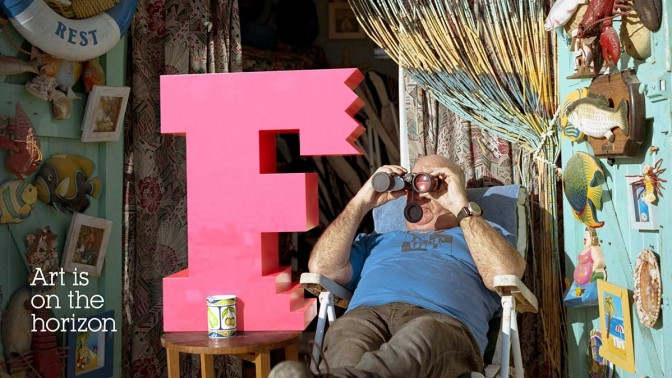 A man looks out with binoculars from his highly decorated beach hut, a giant F - the Brighton Festival logo - is on the table next to him. Captioned 'Art is on the horizon'
