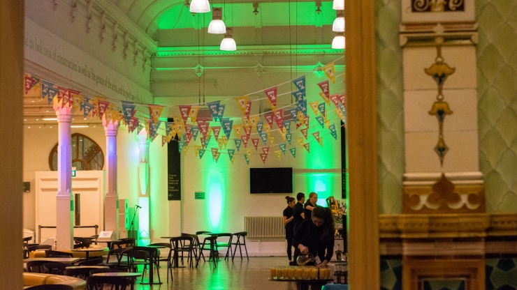 Brighton Dome Foyer being prepared for an event, lit up in green with bunting across the ceiling