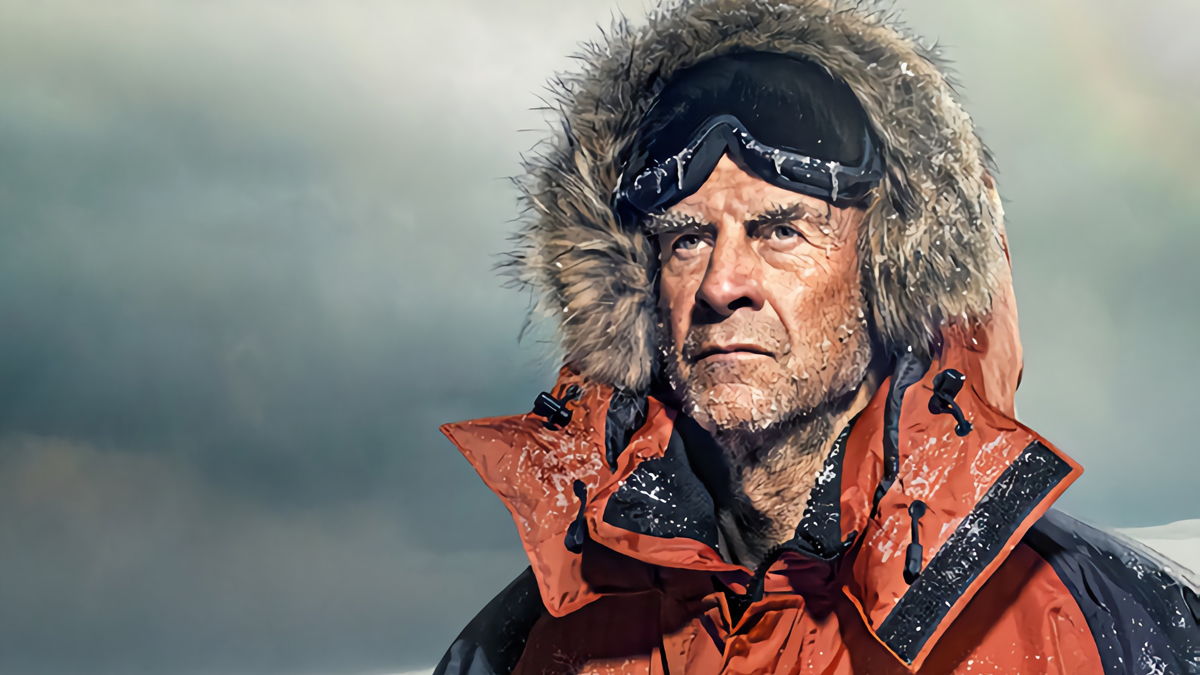 Explorer Sir Ranulph Fiennes wearing a winter coat with snow and ice on it, with a grey icy background.