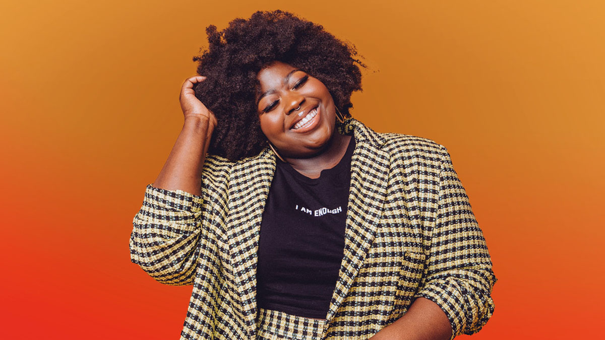 Steph Yeboah smiling, wearing a black t-shirt with white writing 'I Am Enough' and a yellow and black checked blazer. The background is a gradient from yellow at the top to red at the bottom