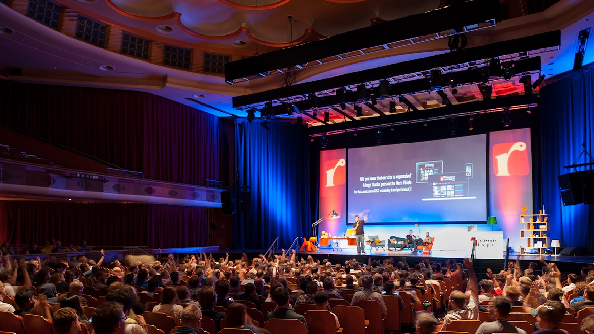 Brighton Dome Concert Hall with a full audience at a conference/ talk, with a large display screen at the back of the stage
