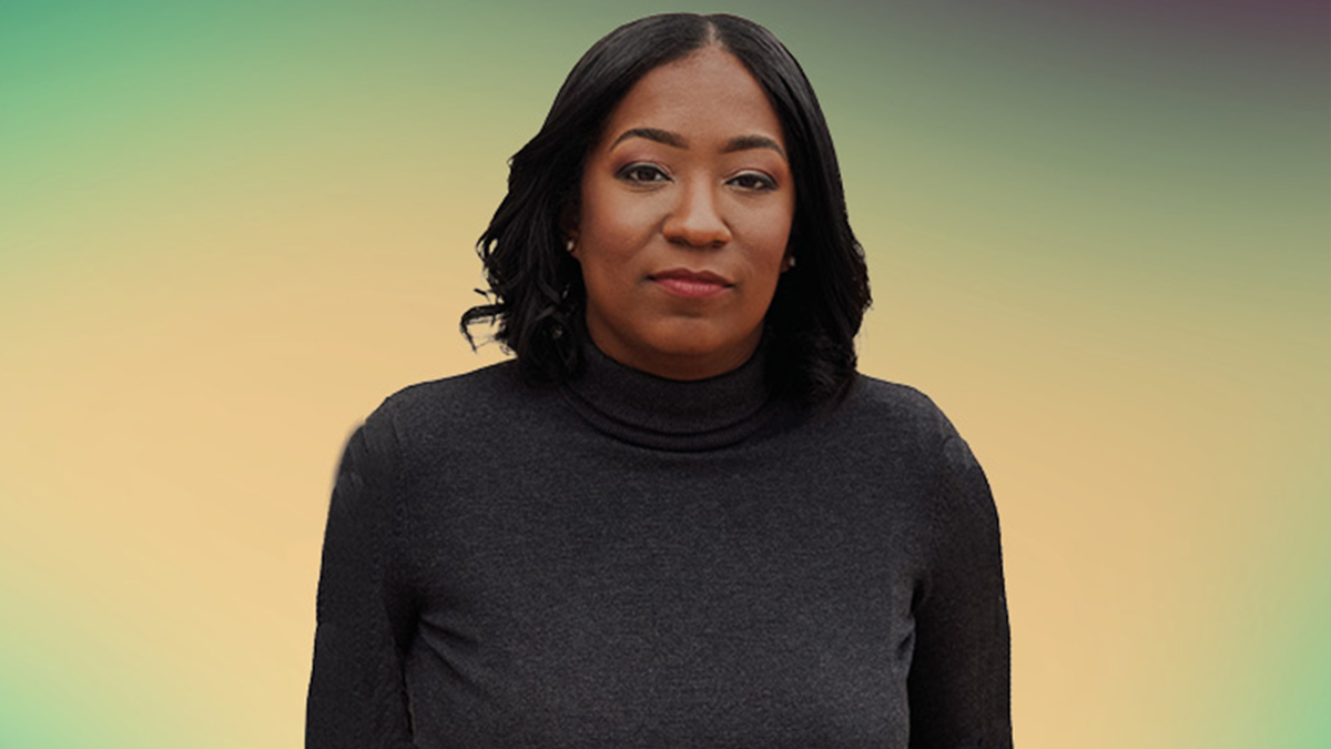 Britt Bennett wearing a black roll-neck top, with a background fading from green around the outside to yellow in the centre
