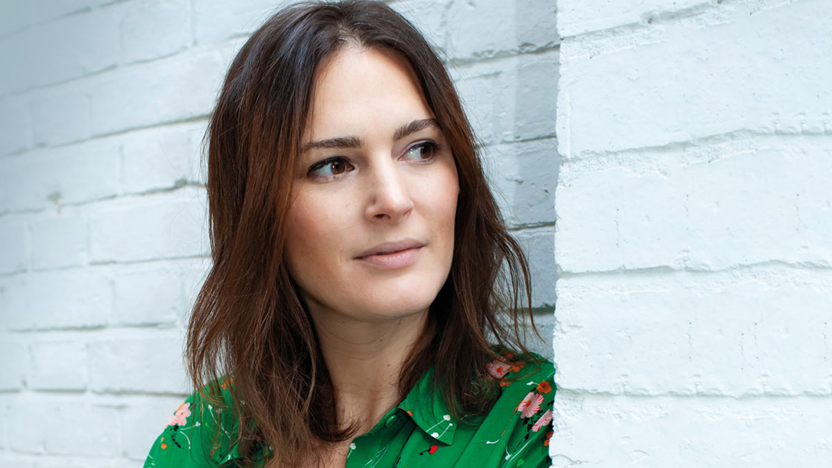 Elizabeth Day wearing a green patterned shirt, standing against a white brick wall, looking off to the right