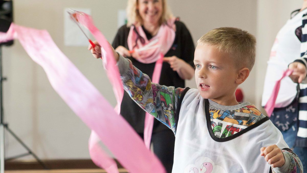 A young boy plays with a streamer at Umbrella Club and Flamingo Chick's workshop at Brighton Dome