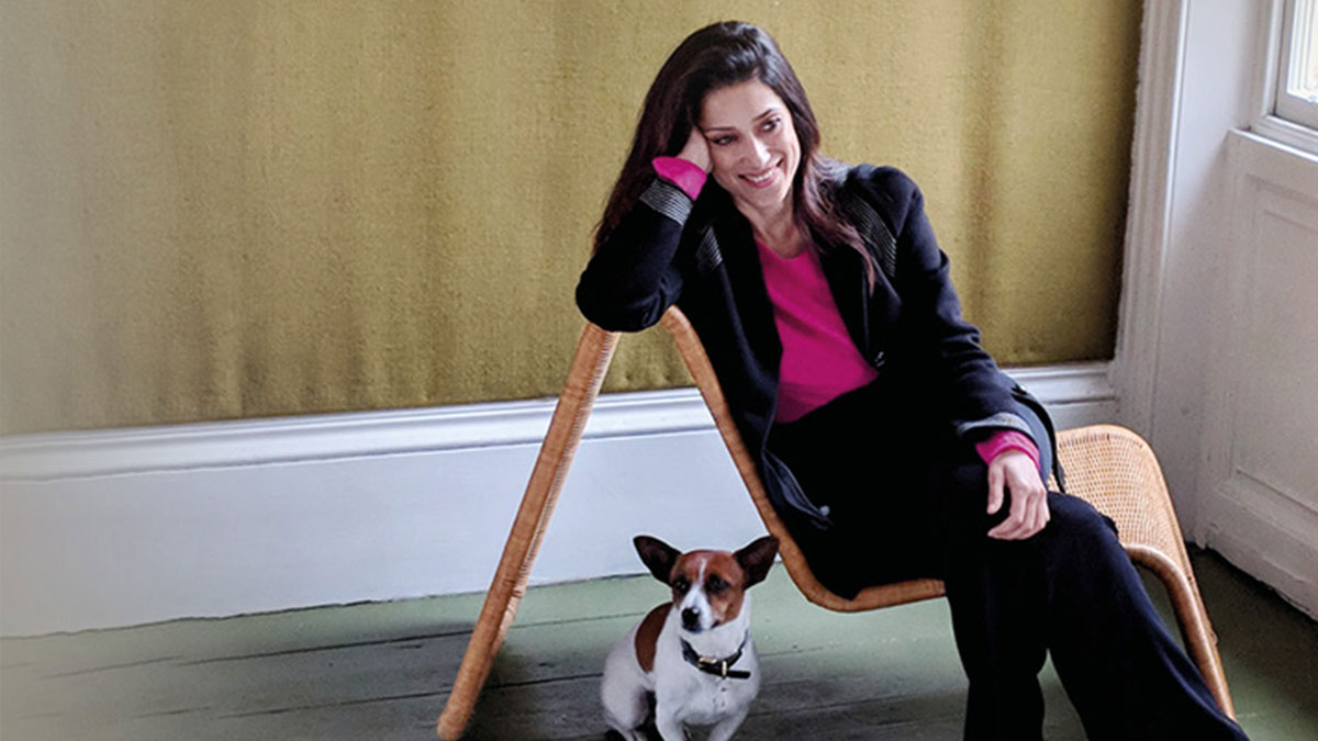 Fatima Bhutto sitting sideways on a chair, wearing a suit and pink shirt, with a dog sitting to the left of her