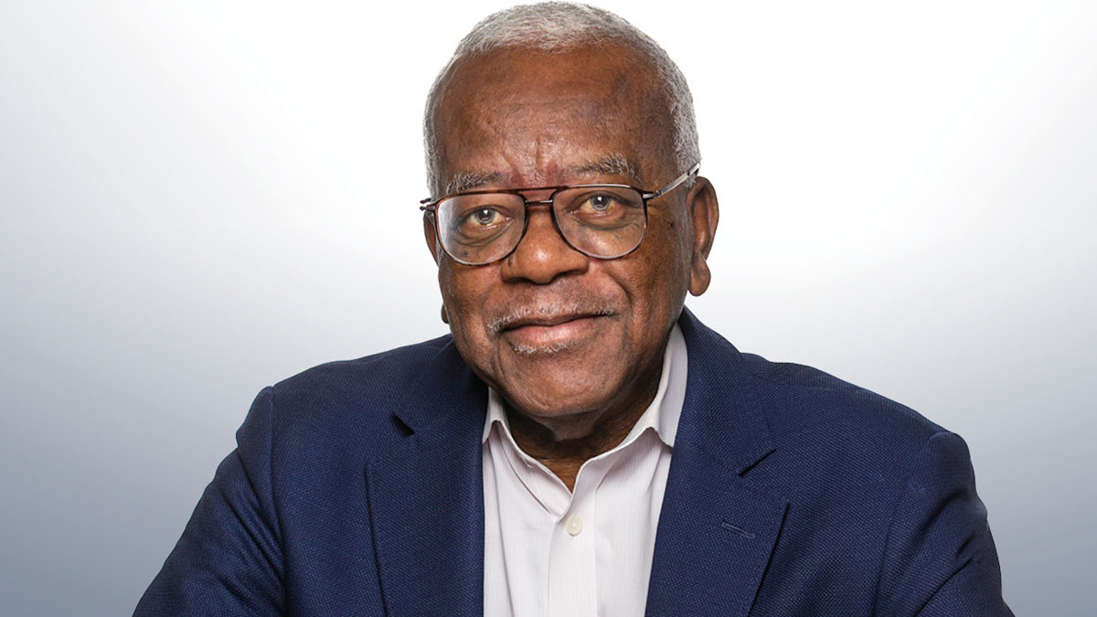 A headshot photo of Trevor McDonald wearing a white shirt, navy blue blazer and glasses, against a white background