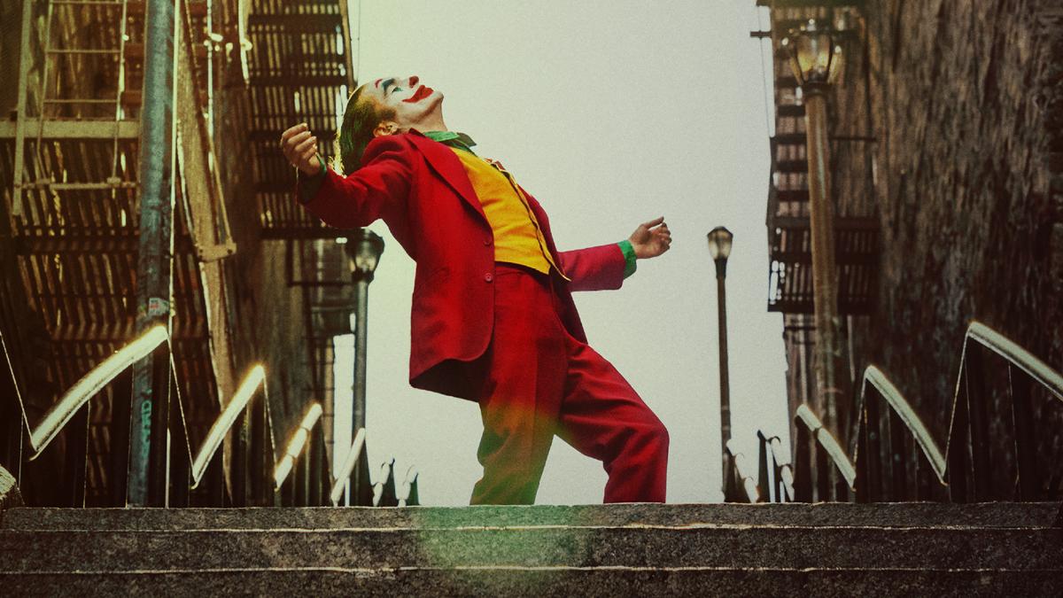 Still image from Joker (2019) of the Joker on steps outside, wearing Joker make-up, a green shirt, yellow vest, red blazer and trousers