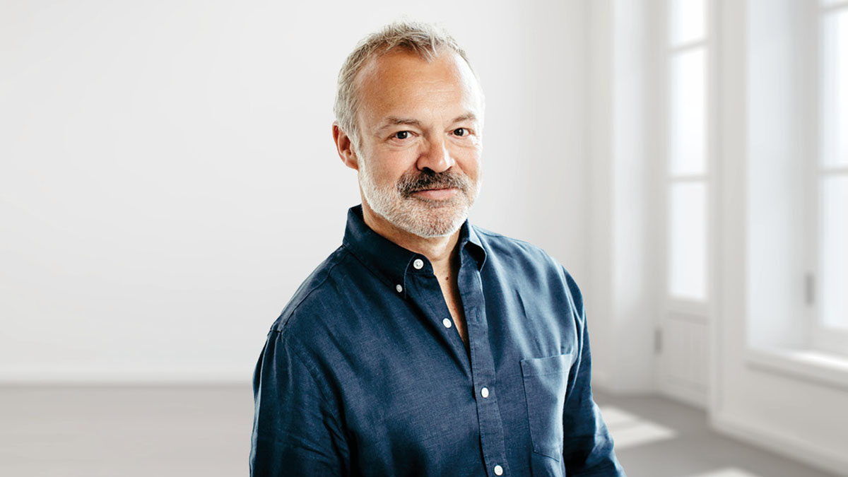 Graham Norton standing in a white room with large bright windows, wearing a dark blue shirt and smiling